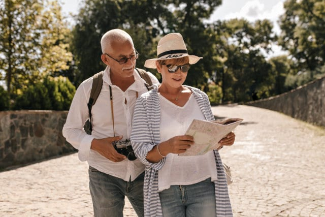 Stylish lady with short hair in hat, glasses and blue blouse looking in map.